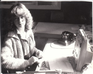 Caron Eastgate as a cadet reporter, Central Hawke's Bay Press, 1979. Note the manual phone. The typewriter is pushed up like that to indicate that I've finished my story and will now work on another. I'm also balancing my cheque book. I had to leave home to come to this job, and when I went to the bank to enquire about a cheque account, they told me I wasn't old enough to have one. When I said I was a reporter, however, they made an exception.