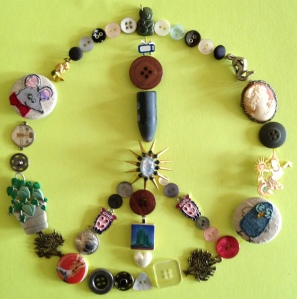 """Peace is Possible"", by Caron Eastgate Dann:  I put together this makeshift peace sign out of bits and bobs—buttons, brooches, earrings (I always knew those buttons you get in tiny plastic packets when you buy something new would come in handy one day)."